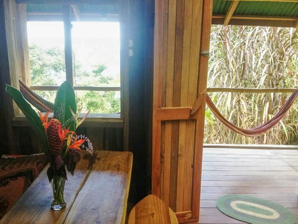 A dining area with fresh flowers at the Pantai Cabin.